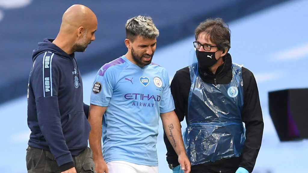 Guardiola and a medic team member escort Aguero off the pitch post his injury